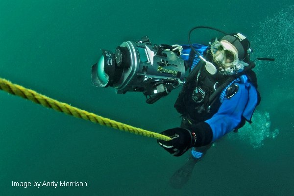 Underwater image of diver Greg Lashbrook accending a yellow rope holding a large underwater video camera