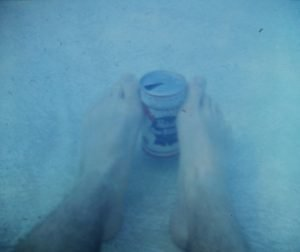 Old faded photograph of a man's feet holding a beer can underwater